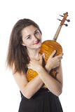Brunette stands and holds violin in studio against white backgro Stock Images