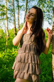 Brunette stands near the birch in forest. Royalty Free Stock Image