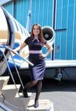 Brunette stewardess on the steps of business jet Stock Photo