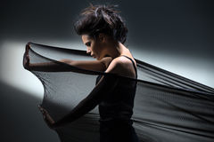 Brunette stretches stretch mesh fabric in front of Royalty Free Stock Photo