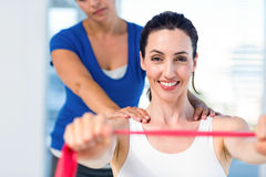 Brunette stretching with her coach and pink cloth Royalty Free Stock Photos