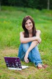 Brunette student girl in the park with notebook Stock Photos