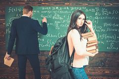 Brunette student with heap of books and heavy rucksack holding her glasses. College girl standing in front of green royalty free stock photos