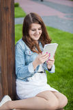 Brunette student reading book on tablet at park on grass Royalty Free Stock Images