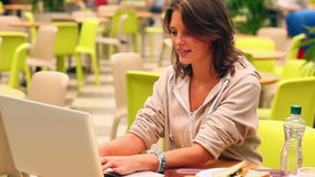 Brunette student studying and drinking water in canteen Royalty Free Stock Photography
