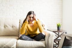 Woman Massaging Her Head At Home. Brunette suffering from migraine while sitting in living room royalty free stock images