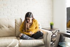 Woman Having Abdominal Pain. Brunette suffering from stomach ache while sitting on sofa stock photos