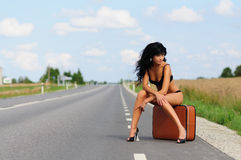 Brunette with suitcase in road, highway. Stock Images