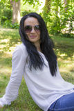 Brunette in sunglass sitting on green grass Royalty Free Stock Photo