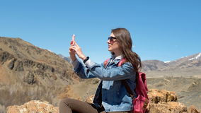 Brunette in sunglasses and pink backpack makes a photo of a spring canyon with a river 4k. stock footage