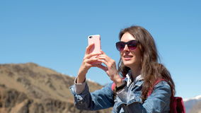 Brunette in sunglasses and pink backpack makes a photo of a spring canyon with a river 4k. stock video