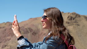 Brunette in sunglasses and pink backpack makes a photo of a spring canyon with a river 4k. Brunette 20s girl in sunglasses, denim jacket and pink backpack makes stock video footage