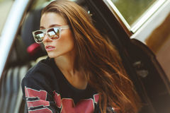 Brunette in sunglasses sitting in car, tinted photo. Brunette in sunglasses sitting in burgundy car, tinted photo Stock Photos