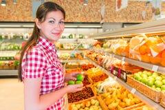 Brunette in supermarket chooses the lemons Royalty Free Stock Photo