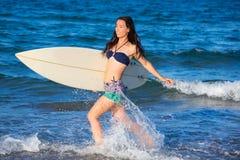 Brunette surfer girl running in the beach Stock Photo