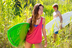 Brunette surfer girl walking in the jungle Stock Photography