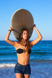 Brunette surfer teen girl holding surfboard in a beach Royalty Free Stock Images