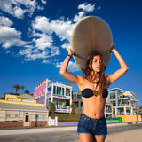 Brunette surfer teen girl holding surfboard in a beach Royalty Free Stock Photo