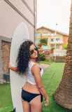Brunette surfer woman with top and bikini holding Royalty Free Stock Photo