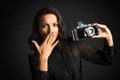 Brunette surprised woman holding  vintage camera Stock Image