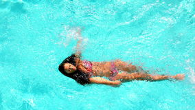 Brunette swimming across the pool on sunny day stock video footage