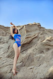 Brunette in swimsuit on a sandy beach in the evening sun. Beauti. Ful woman posing against the backdrop of sandy mountains Royalty Free Stock Photos