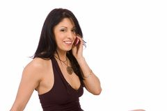 A brunette talking on her cell phone. An isolated beautiful hispanic model talking on her cell phone Royalty Free Stock Images