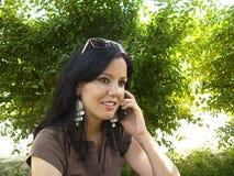 Brunette talking on mobile phone Stock Photo