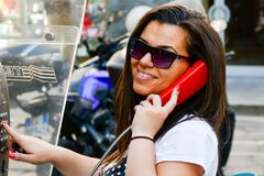Brunette talking at Public phone box. Smiling brunette talking at Public phone box in Mlan, Italy Royalty Free Stock Photos