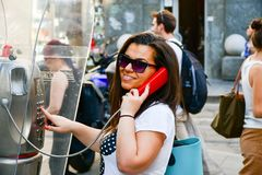 Brunette talking at Public phone box. Smiling brunette talking at Public phone box in Mlan, Italy Stock Photography