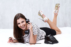 Brunette talking on the retro phone Stock Photography