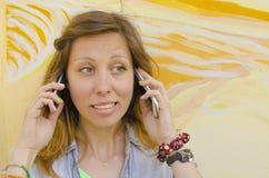 Brunette talking on two mobile phones Stock Photo