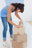 Brunette taping up moving boxes Royalty Free Stock Photo