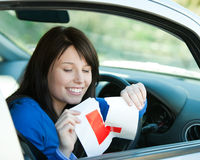 Brunette teen girl in her car tearing a L-sign Stock Photography