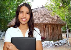 Brunette teen student indian latin holding laptop. Traditional cabin hut jungle Stock Image