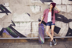 Brunette teenage girl in hipster outfit (jeans shorts, keds, plaid shirt, hat) with a skateboard at the park Royalty Free Stock Image