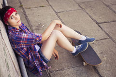 Brunette teenage girl in hipster outfit (jeans shorts, keds, plaid shirt, hat) with a skateboard at the park outdoors Royalty Free Stock Photos