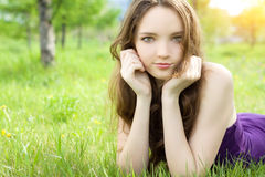 Brunette teenager girl lying on meadow Royalty Free Stock Photos