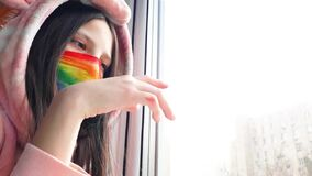 Brunette teenager girl in a medical mask painted in bright rainbow colors stands at window with her hand on glass.Concept of
