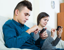Brunette and teenager looking at screens of smartphones Stock Photography