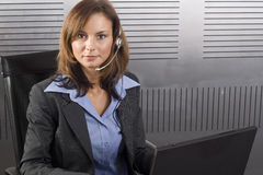 Brunette Telesales PC. Young attractive brunette call center agent talking on the headset in a modern office setting with laptop Royalty Free Stock Photo
