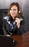 Brunette Telesales PC. Young attractive brunette call center agent talking on the headset in a modern office setting with laptop Stock Image