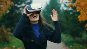 Brunette testing latest augment reality producing equipement VR headset using her hands. Portrait of happy brunette girl in black coat game tester finally stock footage