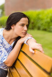 Brunette thinking and sitting on bench Stock Image