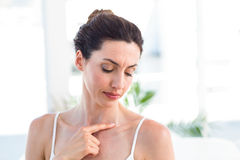 Brunette touching her clavicle. In medical office royalty free stock photos