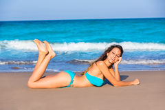 Brunette tourist lying in beach sand tanning happy Royalty Free Stock Photo