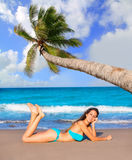 Brunette tourist lying in beach sand tanning happy Stock Photo