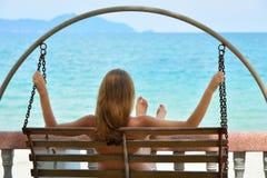 Brunette träumt auf einem Schwingen gegen das Meer Stockbilder