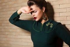 Brunette-traurige Frau im grünen Kleid über Backsteinmauer Stockbild