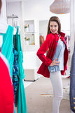 Brunette trying on a red coat Stock Photography
